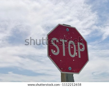 Rural stop sign in Wyoming with bullet holes.