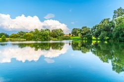 Rural summer landscape reflected in the pond. Blue sky, white clouds and lush green trees.