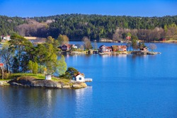 Rural Swedish landscape with coastal villages. Wooden houses and barns on islands in sunny summer day