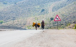 Rural turkish woman with donkey greeting with hand.