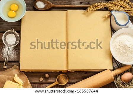 Rural vintage wood kitchen table with blank cook book, baking cake ingredients (eggs, flour, milk, butter, sugar) and cooking utensils around. Country background with free recipe text space.
