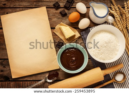 Rural vintage wooden kitchen table with old blank sheet of paper and baking cake ingredients (chocolate, eggs, flour, milk, butter, sugar). Background layout with free recipe text space.