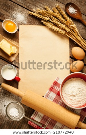 Rural vintage wooden kitchen table with old blank sheet of paper, baking cake ingredients (eggs, flour, milk, butter, sugar) and cooking utensils around. Background with free recipe text space.
