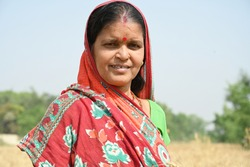 Rural woman standing in agriculture field, she is wearing traditional cloth