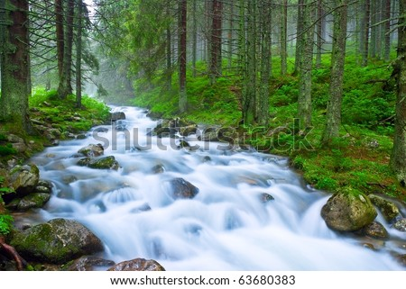 rushing blue river in a mountain forest - stock photo