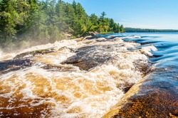 Rushing white water flows rapidly down Curtain Falls in a remote area of Minnesota known as the Boundary Waters Canoe area, bordering Quetico National Park in Canada.