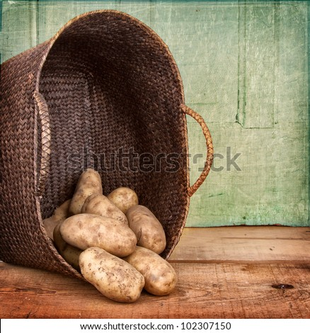 Russet potatoes spilling out of a basket on wooden crate, grunge background