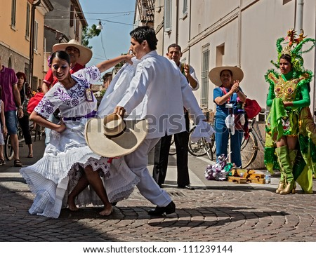 "RUSSI, ITALY  - AUGUST 5:  A couple of Peruvian dancers in white dress performs traditional courting dance ""la marinera"" at International folk festival on August 5, 2012 in Russi, Ravenna, Italy"