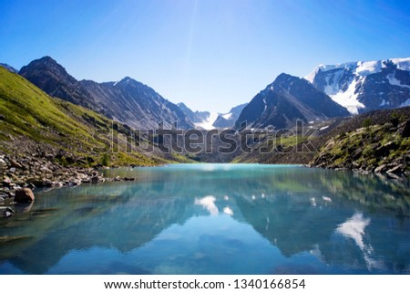 Russia, Altai, mountains. Beautiful blue lake Kucherla in the foreground against the snow-capped peaks of high mountains. Summer vacation in the mountains. reflection of mountains with snow-capped #1340166854