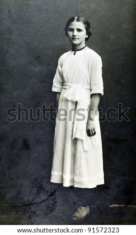 RUSSIA - CIRCA 1902: Old photo printed in Russia shows young girl in white dress, circa 1902