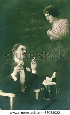 RUSSIA - CIRCA 1915: Retro postcard depicts a man with a cigarette and a glass of wine who dreams about a girl, circa 1915, Russia. Vintage hand-tinted photograph