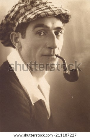 Russia, - CIRCA 1959s: An antique studio portrait of young man in a cap, Smoking pipe.