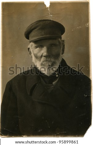 RUSSIA - CIRCA 1920s: Portrait of an elderly man with a gray beard in a dark coat and cap, circa 1920s