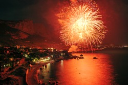 RUSSIA, Crimea. Celebration party on the beach with fireworks, small resort town. Holiday event background, bright colorful explosion of firework, glow light