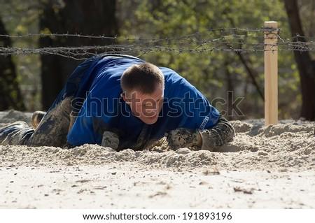 RUSSIA, DMITROV REGION, SHUKOLOVO VILLAGE - APRIL 26: Unidentified man crawling on sand on survival festival game NaPredele (On the edge) on April 26, 2014, in Dmitrov region, Shukolovo, Russia