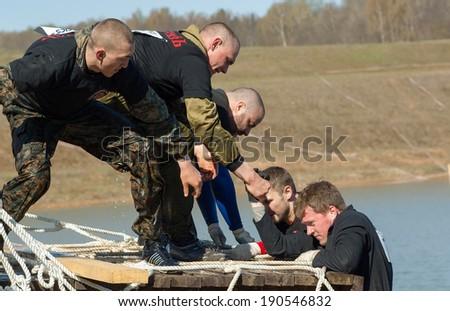 RUSSIA, DMITROV REGION, SHUKOLOVO VILLAGE - APRIL 26: Unidentified men on net stair on survival festival game NaPredele (On the edge) on April 26, 2014, in Dmitrov region, Shukolovo village, Russia