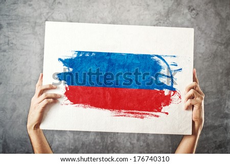 Russia flag. Man holding banner with Russian Flag. Supporting national team, patriotism concept.