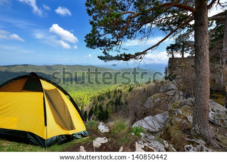 Russia. Lagonaki plateau. Adygea. Mountains in early spring, yellow camping tent on a shore in a morning light