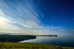 Russia, Lake Baikal, Olkhon Island, Clouds and Stars on the Small Sea Bay. Cape Sagan-Khushun