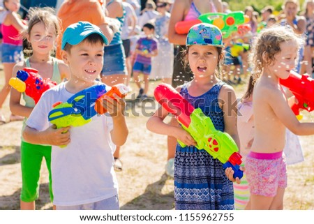 Russia. Moscow. August 11, 2018 Children playing outdoors with water cannons on a beautiful sunny day. Water battle, water game battle #1155962755