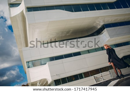 Russia, Moscow 01 October - 2016: Fashion model against Zaha Hadid Dominion Tower exterior, Moscow, Russia