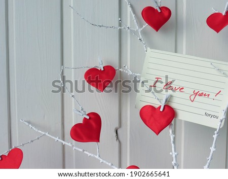 Russia, Moscow region, Lobnya, 01.25.2021: Note 'I love you!' on a white twig decorated with red hearts. On a white wooden background Сток-фото ©