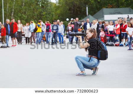 Russia. Novosibirsk. 13 Aug 2017.Beautiful girl photographer with a big lens on a city-wide celebration of photographs of people #732800623