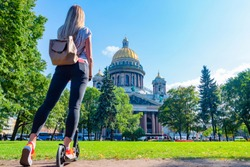Russia. Saint Petersburg. Girl in front of St. Isaac's Cathedral. A girl walks around Petersburg. Woman with a scooter. A young girl admires the St. Isaac's Cathedral. Walking in St. Petersburg.