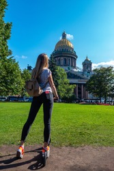 Russia. Saint Petersburg. Saint Isaac's Cathedral. The girl on the scooter. Girl on a scooter in Petersburg. A student looks at St. Isaac's Cathedral. Tours in St. Petersburg. Traveling in Russia.
