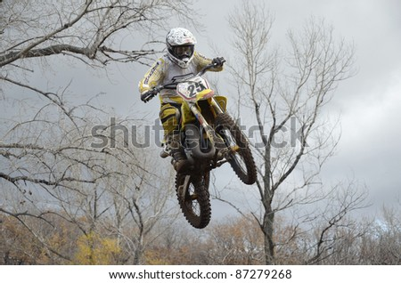 "RUSSIA, SAMARA, CHAPAYEVSK - OCTOBER 17: A jump rider unknown on the background an autumn forest the Open Cup ""Volga"" motocross on October 17, 2011 in Chapayevsk, Samara, Russia"