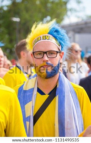 Russia, Samara, July 2018: football fan from Sweden with a painted face in national colors before the match England Sweden at the World Cup. #1131490535