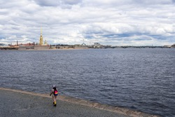 Russia, St. Petersburg, Vasilievsky Island. Granite embankment. Cloudy spring day. On the horizon is spire of the Peter and Paul Fortress against backdrop of grey clouds. Girl shooting by smartphone.