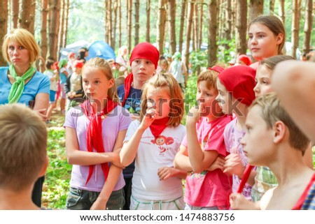 RUSSIA, YAROSLAVL - 30 JUN 2012: group happy children and adult teens relax in summer forest tent camp play active games on banks Volga river participate in competitions on bright Sunny day #1474883756