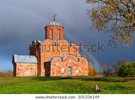 Russian ancient brick church against a rainbow
