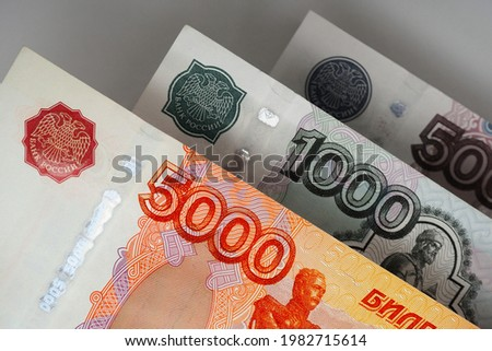 Russian banknotes 5000, 1000 and 500 rubles close up. Bright expressive illustration about economy and money of Russia. Nearest bill is highlighted in vivid color, other notes are pale. Macro Сток-фото ©