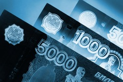 Russian banknotes 5000, 1000, and 500 rubles close up. Dark dramatic black and blue illustration about economy and money of Russia. Inverting. Macro