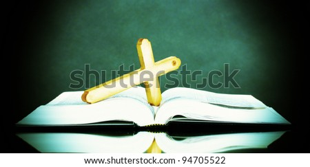 Russian bible and wooden cross on black background