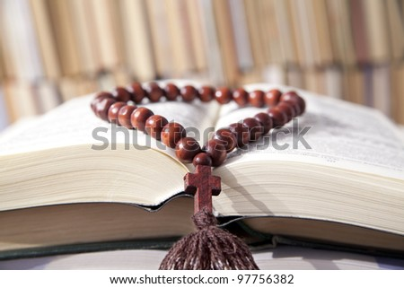 Russian bible and wooden rosary on the background of the library bookshelves