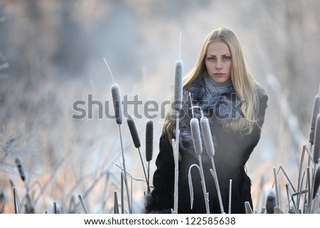Russian blonde with beautiful long hair, freezing in winter fur coat and gloves