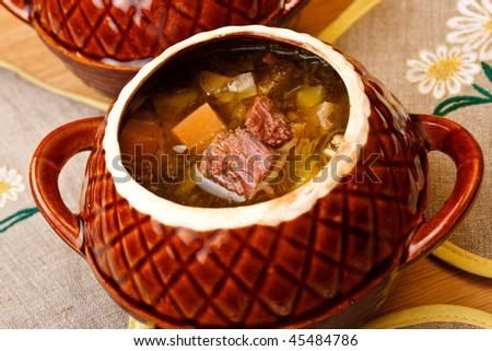 Russian cabbage soup with beef in ceramics pot