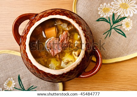 Russian cabbage soup with meat in pot (top view)