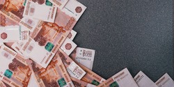 Russian cash banknotes of five thousand rubles, scattered on a gray background