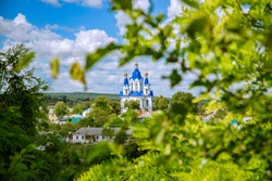 Russian country side village spring time view of orthodox church facade landmark view in green leaves foliage natural frame foreground in clear weather bright day