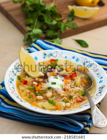 Russian dishes - cabbage soup with white beans, lemon and sour cream.