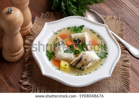 Russian Fish Soup Ukha. White fish in a clear broth with diced root vegetable served in white plate on wooden table. Selective focus. 商業照片 ©