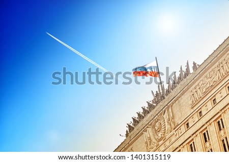 russian flag waving on top of ministry of defense building in moscow city russia against blue sky with airplane flying high aerial view of aircraft contrail and old stalin era architecture landscape #1401315119