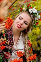 Russian girl in national dress in the autumn garden