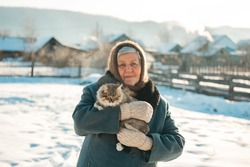 Russian grandmother holds a kitten in her arms, village, Siberia, winter