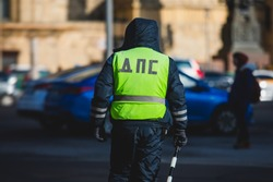 Russian Inspector of traffic police highway patrol regulates the movement of transport in the center of Moscow, in yellow vest jacket with a sign