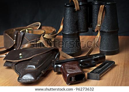 russian 9mm handgun PM (Makarov) on the table with holster, belt, binocular and empty pistol holder - stock photo